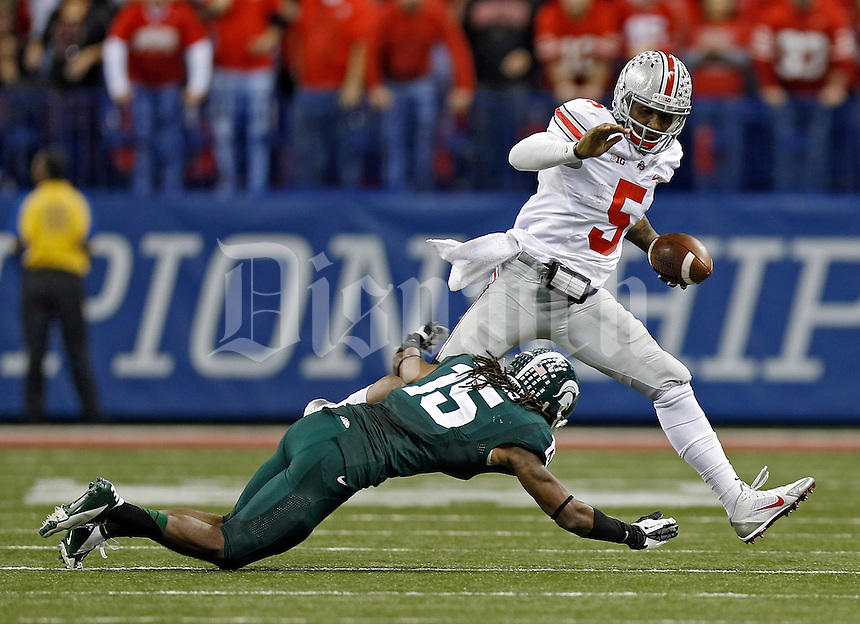 Ohio State Buckeyes quarterback Braxton Miller (5) jumps over Michigan State Spartans cornerback Trae Waynes (15) in the 2nd quarter during the Big 10 Championship game at Lucas Oil Stadium in Indianapolis, Ind on December 7, 2013.  (Dispatch photo by Kyle Robertson)