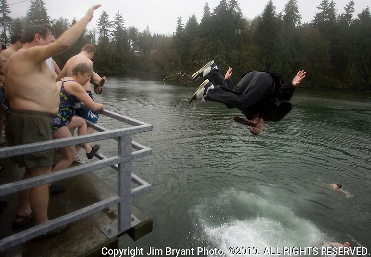 Kevin Morgan (R) performs a front flip as he jumps from a bridge into the Burley Lagoon in Olalla, Washington on 1 January  2010. Over 300 hardy participants  braved the chilly lagoon waters to join in on the annual New Year's Day Tradition.  Jim Bryant Photo. ©2010. ALL RIGHTS RESERVED.