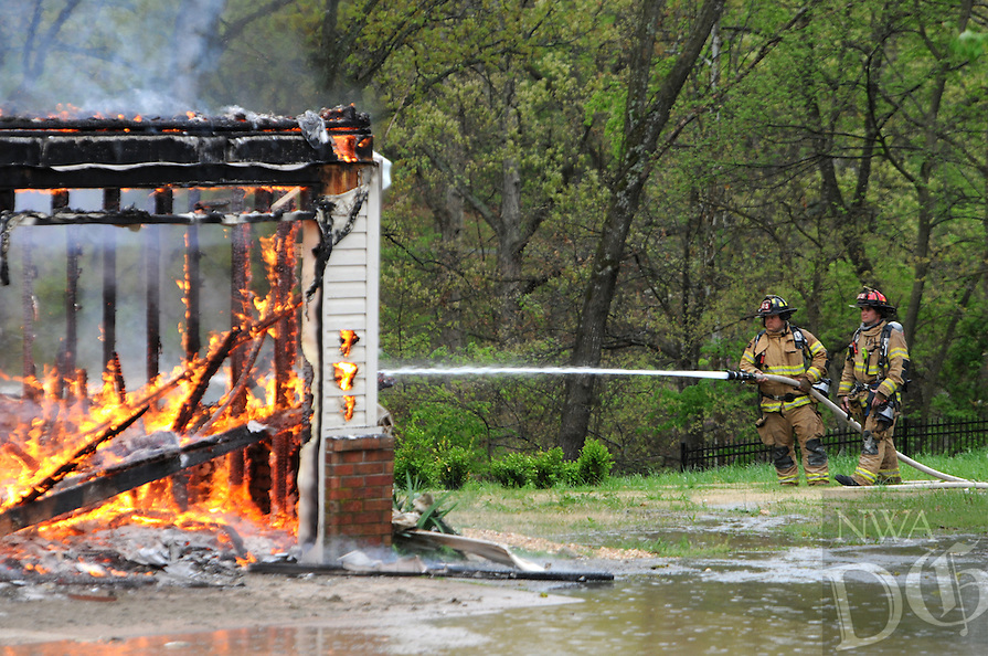 NWA Democrat-Gazette/ J.T. WAMPLER -- Rogers firefighter Justin Blickenderfer, left, and Captain Joey Everhart spray water onto a house on fire in southwest Rogers Monday April 13, 2015. The department was conducting a training fire so new recruits could get some experience.