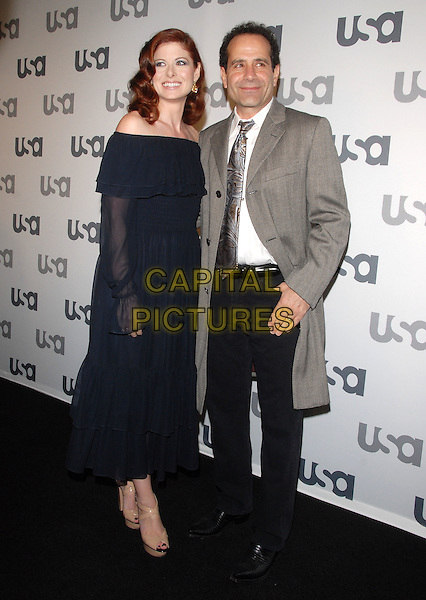 DEBRA MESSING & TONY SHALHOUB .The USA Network 2008 Upfront held at Craft in Century City, California, USA..April 3rd, 2008                                         .full length black dress off the shoulder sheer sleeves grey gray coat jacket tie trousers.CAP/DVS.©Debbie VanStory/Capital Pictures.