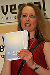 Kathleen Maddy, with her book 'Gold Rays', gives a speech at the event..Picture: Shane Maguire / www.newsfile.ie.
