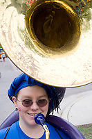 Happy woman age 22 band member holding her sousaphone tuba. MayDay Parade and Festival. Minneapolis Minnesota USA