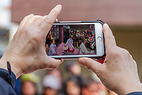 A visitor uses a smartphone to film shrine maidens doing a ritual dance at the beginning of the Kanamara matsuri or festival of the Steel phallus Kawasaki Daishi, Kawasaki, Kanagawa, Japan. Sunday, April 2nd 2017. The Kanamara Penis festival takes place on the first Sunday of April and celebrates the local legend of a penis eating demon who was defeated after being tricked into biting a steel phallus. The festival is popular with Japan's gay community and now uses its notoriety to raise money for HIV and AIDS charities. It is also wildly popular with foreign and Japanese.tourists.
