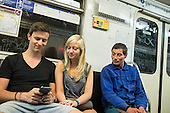 Two young people look at a mobile phone on the Budapest metro.