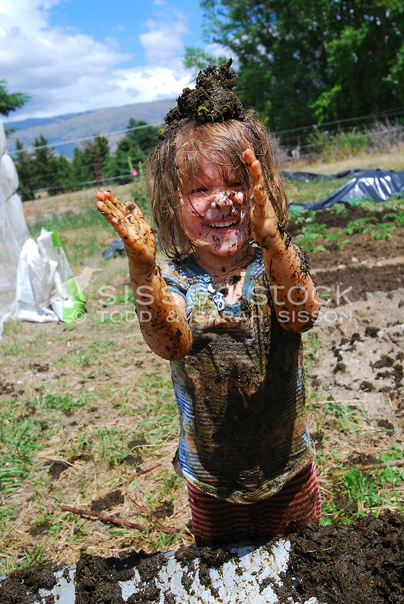 Three year old girl smiling and covered in mud while playing in the garden, New Zealand - stock photo, canvas, fine art print