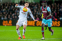 Federico Fernandez of Swansea tries to keep the ball away from Cheikhou Kouyate of West Ham United during the Barclays Premier League match between Swansea City and West Ham United played at the Liberty Stadium, Swansea  on December 20th 2015