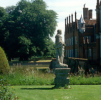 A weathered statue stands in the 15th century surroundings of the moated Helmingham Hall in Suffolk