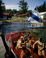 Group of friends in a wooden boat & sailboat. 1965 photograph.
