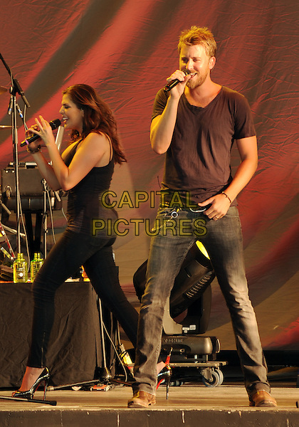 "LADY ANTEBELLUM - Hillary Scott & Charles Kelley .Country music group LADY ANTEBELLUM performs as the opening act for Tim McGraw's ""Southern Voice Tour 2010"" held at the First Niagara Pavilion, Pittsburgh, Pennsylvania, USA..July 8th, 2010.stage concert live gig performance music full length black top jeans denim singing walking profile .CAP/ADM/DS.©Devin Simmons/AdMedia/Capital Pictures."