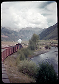 RGS eastbound freight train approaching Telluride along San Miguel River as seen from the caboose.<br /> RGS  Keystone, CO  Taken by Rasmussen, Forest - maybe 7/17/1951