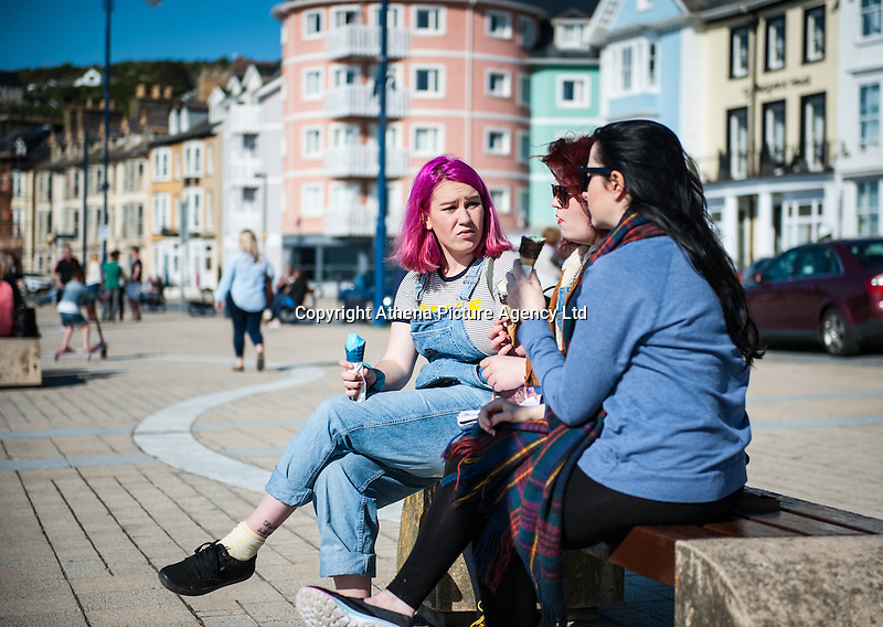 Aberystwyth, West Wales, UK Weather: Young women enjoy an ice cream in Aberystwyth promenade.