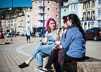 Aberystwyth, West Wales, UK Weather: Young women enjoy an ice cream in Aberystwyth promenade.