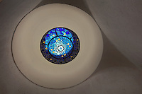 Circular stained glass window in blue glass with design of circles, made by Ateliers Loire, Chartres, in the ceiling of the staircase in the Bell tower, in Le Tresor de la Cathedral d'Angouleme, in Angouleme Cathedral, or the Cathedrale Saint-Pierre d'Angouleme, Angouleme, Charente, France. The 12th century Romanesque cathedral was largely reworked by Paul Abadie in 1852-75. In 2008, Jean-Michel Othoniel was commissioned by DRAC Aquitaine - Limousin - Poitou-Charentes to display the Treasure of the Cathedral in some of its rooms, which opened to the public on 30th September 2016. Picture by Manuel Cohen. L'autorisation de reproduire cette oeuvre doit etre demandee aupres de l'ADAGP/Permission to reproduce this work of art must be obtained from DACS.