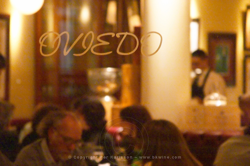 The main dining room at the restaurant full with dining guests and waiters serving through a glass window with the name engraved. The Oviedo Restaurant, Buenos Aires Argentina, South America