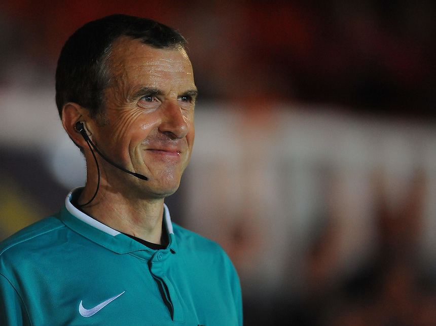 Linesman Simon Knapp can't help but smile at protests against a stoppage<br /> <br /> Photographer Kevin Barnes/CameraSport<br /> <br /> Football - The Football League Sky Bet League Two - Newport County AFC v Cambridge United - Monday 8th September 2014 - Rodney Parade - Newport<br /> <br /> &copy; CameraSport - 43 Linden Ave. Countesthorpe. Leicester. England. LE8 5PG - Tel: +44 (0) 116 277 4147 - admin@camerasport.com - www.camerasport.com