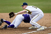 Michigan Wolverines first baseman Kendall Patrick (15) catches a pickoff attempt at first base during the NCAA baseball game against the Washington Huskies on February 16, 2014 at Bobcat Ballpark in San Marcos, Texas. The game went eight innings, before travel curfew ended the contest in a 7-7 tie. (Andrew Woolley/Four Seam Images)