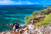 Happy couple standing along the edge of the trail and enjoying a view of the clear ocean and the reefs of Maui.
