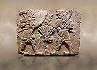 Aslantepe Hittite relief sculpted orthostat stone panel of Lion Men. Limestone, 1399-1301 BC. Anatolian Civilisations Museum, Ankara, Turkey.<br /> <br /> There are two lion-men with a sword at their waists on both sides of the tree of life. The figure on the right holds a sickle in his left hand resting on his shoulder and a symbol his right hand. The figure on the left carries a double-faced ax in his right hand. <br /> <br /> Against a brown art background.