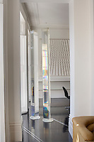 Amongst the many artworks that decorate the open plan apartment is a pair of Perspex columns in the dining area