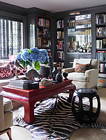 The library's sofa by Restoration Hardware is covered in a Perennials fabric, the vintage club chairs, upholstered in a Great Plains linen are from Duane; the cocktail table is Chinese and the stool came from the former Manhattan nightclub Moomba; the zebra skin is antique, the blinds are by Hunter Douglas and the walls are painted in Dragon's Breath by Benjamin Moore.