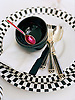 (bottom to top) Fronasetti round tray; Astier de Villatte 'Empire' plate; 'Talisman' fork & knife & tablespoon; Linen and Moore emboidered white napkins; Linen embroidered black napkin; Missoni 'Bianconero' bowls; Two's Company teaspoon.