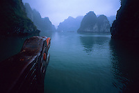 View from bow of traditional Vietnames junk cruising through the misty islands of Halong Bay, Vietnam