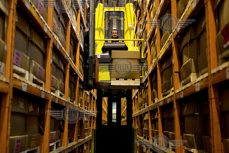 A forklift driver moves boxes of coins in a warehouse at the Royal Mint, near Llantrisant in Mid Glamorgan. As well as producing coinage for domestic use the mint also manufactures coins for around 60 countries worldwide.