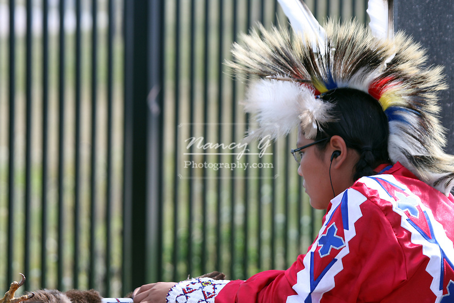 A teenager male Native American Menomonee Indian dancer listening to music at a Pow Wow at the Milwaukee Lakefront Indian Summer Festival, Wisconsin
