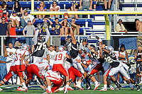9 October 2010:  FIU's special teams unit (defensive tackle Andre Pound (75), defensive end Tourek Williams (97) and linebacker Markieth Russell (22)) attempt to block an extra point attempt as the FIU Golden Panthers defeated the Western Kentucky Hilltoppers, 28-21, at FIU Stadium in Miami, Florida.