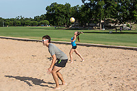 A young attractive couple playing volleyball on Zilker Park sand volleyball courts under blue skies during summer in downtown Austin, Texas.