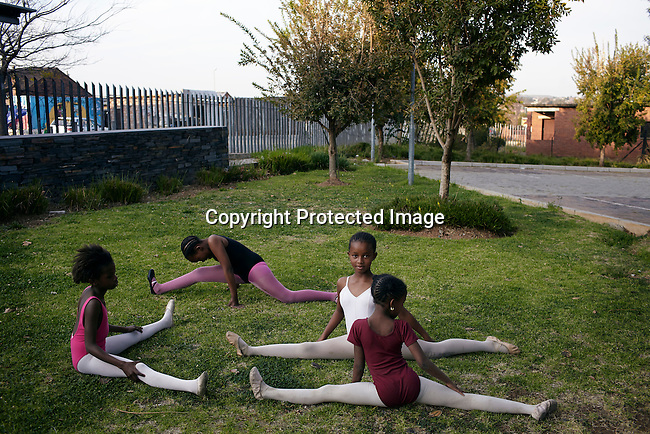 SOWETO, SOUTH AFRICA MAY 20: Ballet students warm up before a class on May 20, 2013 in Orlando section of Soweto, South Africa.  South African Mzansi Ballet runs a project in Soweto teaching young boys and girls classical ballet. Many of the young people growing up have many more opportunities than their parents. Soweto is today a mix of old housing and newly constructed townhouses. A new hungry black middle-class is growing steadily. Many residents work in Johannesburg but the last years many shopping malls have been built, and people are starting to spend their money in Soweto. (Photo by: Per-Anders Pettersson)