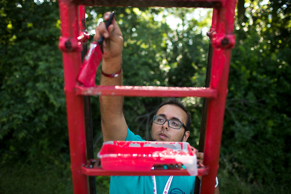 """Nick Stringfellow paints a playground slide during """"Circle the City with Service,"""" the Kiwanis Circle K International's 2015 Large Scale Service Project, on Wednesday, June 24, 2015, at the Friendship Westside Center for Excellence in Indianapolis. (Photo by James Brosher)"""