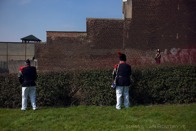 Men in 19th century historical Belgian uniforms take a break from the parade to urinate during the St. Veroon procession in Tubize, Belgium on April 1 2013. Spectators to the procession give drinks to the passing marchers, and soon many of them are stageringly drunk. The procession partially follows the exact border between Flanders and Wallonia.