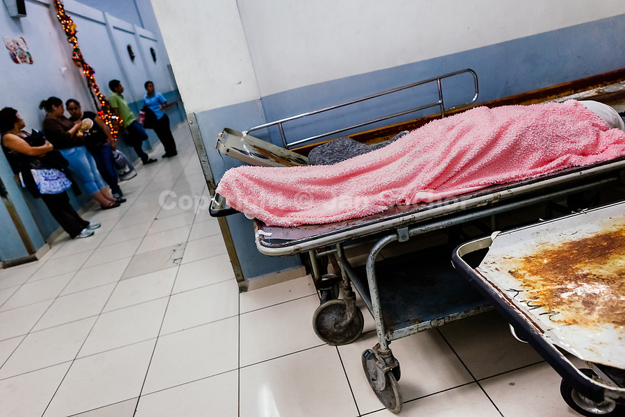 A dead body of a deceased patient, covered by a bath towel, lies on the strecher in the corridor inside the emergency department of a public hospital in San Salvador, El Salvador, 21 December 2015.