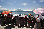 A group of Indigenous women in traditional dress gathering on the shore of Atitlan lake for a baptise ceremony. Panajachel. Guatemala