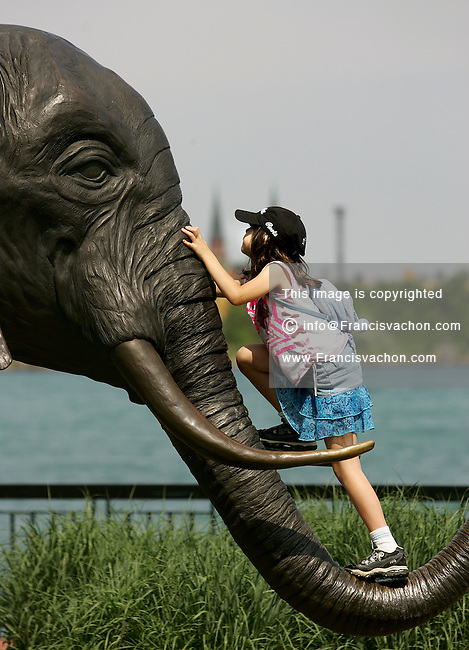 Windsor, Ontario  -  Nicole Vetor climbs the elephant sculpture in Windsor's riverfront Friday June 23, 2006. (Francis Vachon/ Windsor Star)<br />