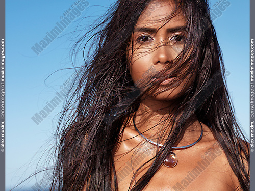 Portrait of a beautiful woman with long wet hair blown in the wind with blue sky in the background