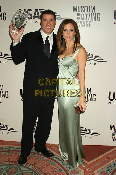 JOHN TRAVOLTA & KELLY PRESTON.American Museum of the Moving Image Salute to John Travolta, Waldorf Astoria Hotel, New York City, New York, USA, December 5th 2004..full length glass trophy green satin dress.Ref: IW.www.capitalpictures.com.sales@capitalpictures.com.©Capital Pictures.