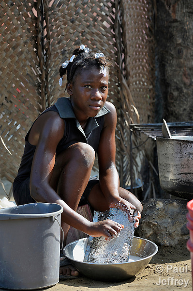 A woman grates food for cooking in the Haitian village of Vaudreuil.