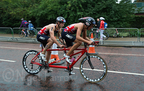 13 SEP 2013 - LONDON, GBR - David Ellis (GBR) (left) of Great Britain negotiates the wet roads on the bike with his guide Luke Watson (right) on his way to winning the men's TRI-6b category in the ITU 2013 World Paratriathlon Championships in Hyde Park in London, Great Britain (PHOTO COPYRIGHT © 2013 NIGEL FARROW, ALL RIGHTS RESERVED)