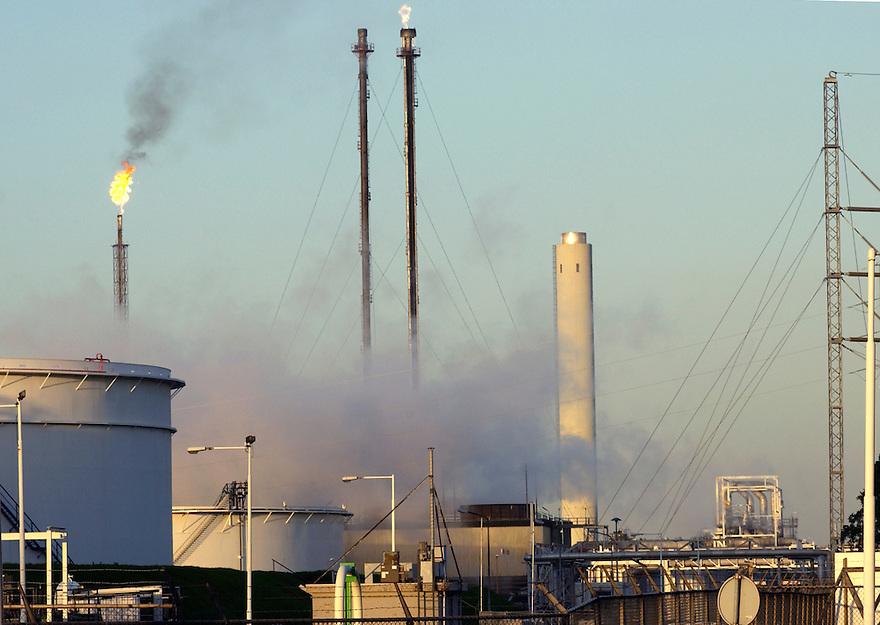 Nederland, Pernis (Rotterdam), 8 sept 2004..Industriegebied. Rokende schoorstenen, vlam op pijp.  Petrochemische industrie, vervuiling, luchtvervuiling, uitstoot co2, milieu..Foto (c) Michiel Wijnbergh