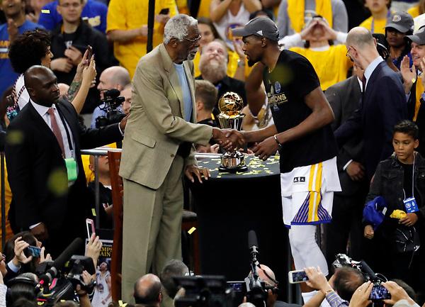 LWS160 - OAKLAND (EE.UU.), 12/6/2017.- El jugador de Golden State Warriors Kevin Durant (d) recibe el trofeo del campeonato de manos del exjugador Bill Russell (i), tras ganar ante Cleveland Cavaliers en el partido cinco del juego de baloncesto de las finales de la NBA en el Oracle Arena de Oakland, California, Estados Unidos, el 12 de junio de 2017. EFE/MONICA M. DAVEY