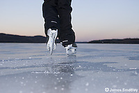 Girl ice skating on a frozen lake in winter