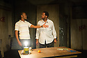 London, UK. 12.02.2014. SIZWE BANZI IS DEAD opens at the Young Vic. Directed by Matthew Xia with lighting design by Ciaran Cunningham and set and costume design by Hyemi Shin. Picture shows: Tonderai Munyevu (Buntu) and Sibusiso Mamba (Sizwe Banzi). Photograph © Jane Hobson.