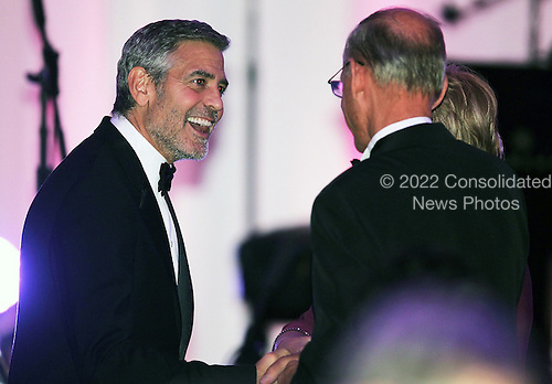 Actor George Clooney (L) is greeted by other guests during a state dinner for British Prime Minister David Cameron at the South Lawn of the White House March 14, 2012 in Washington, DC. Prime Minister Cameron was on a three-day visit in the U.S. and he had talks with President Obama earlier the day.  .Credit: Alex Wong / Pool via CNP