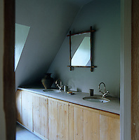 A pair of circular wash basins is set in the stone surface of a bathroom cupboard constructed of simple pine