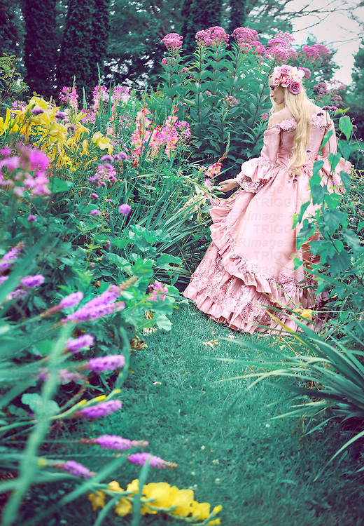 A beautiful princess with long blond hair in her late teens wanders through a garden of pretty flowers, wearing a fancy pink ballgown