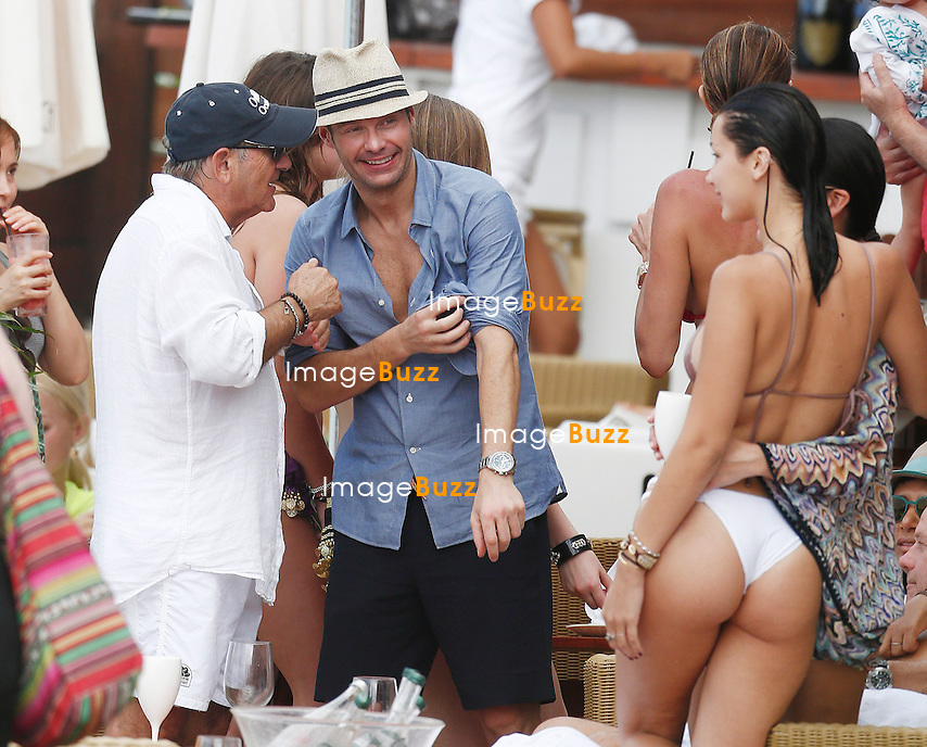 RYAN SEACREST PARTIES WITH BIKINI BABES IN ST. BARTHS. Ryan Seacrest looks to be enjoying himself as he is surrounded by a group of bikini-clad women as he enjoys some drinks in St. Barts<br /> january 2, 2014.