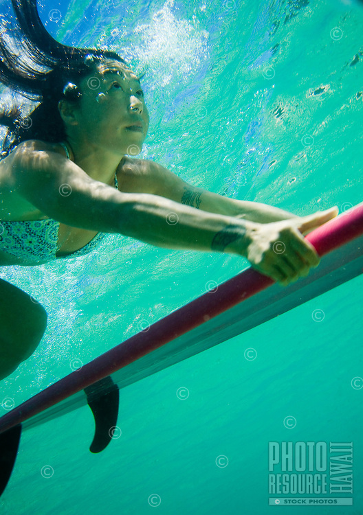 A local Asian woman duck dives a wave at Waimea Bay