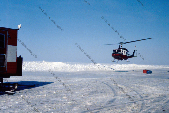 Stock photo showing a Helicopter about to land on a runway built on Beaufor Sea Ice. Helicopters and other aircraft were the only way in or out of the remote exploration geophysical research camps searching for oil out on the ice of the beaufort sea.